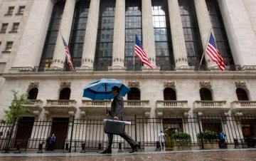 A man carries an umbrella in the rain as he passes the New York Stock Exchange October 16, 2014. REUTERS/Brendan McDermid