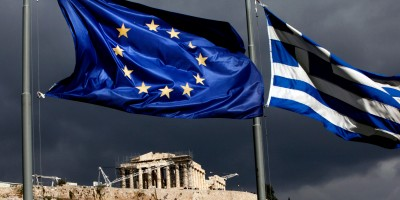 """A European Union (EU) flag, left, and Greek national flag fly near the Parthenon temple on Acropolis hill in Athens, Greece, on Monday, Oct. 31, 2011. Europe's plan to solve the region's debt crisis made credit-default swaps covering Greece """"ineffective,"""" Moody's Investors Service said. Photographer: Angelos Tzortzinis/Bloomberg via Getty Images"""
