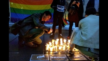 """A man lights a candle during a spontaneous  vigil to remember those slain and wounded at an Orlando nightclub, Sunday June 12, 2016 in Paris. Several people were draped in rainbow flags. They lit candles and took pictures as a person in head-to-toe fetish gear held up a sign saying """"Proud."""" (AP Photo/Raphael Satter)"""